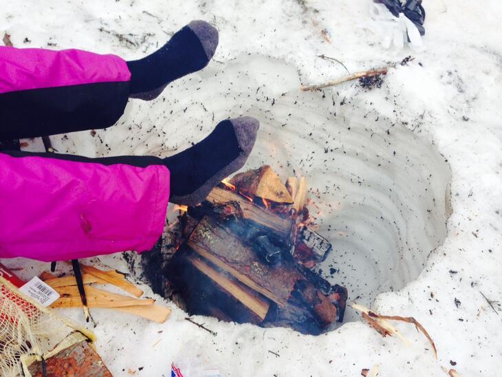 Deltaker varmer føttene over et bål i snøen