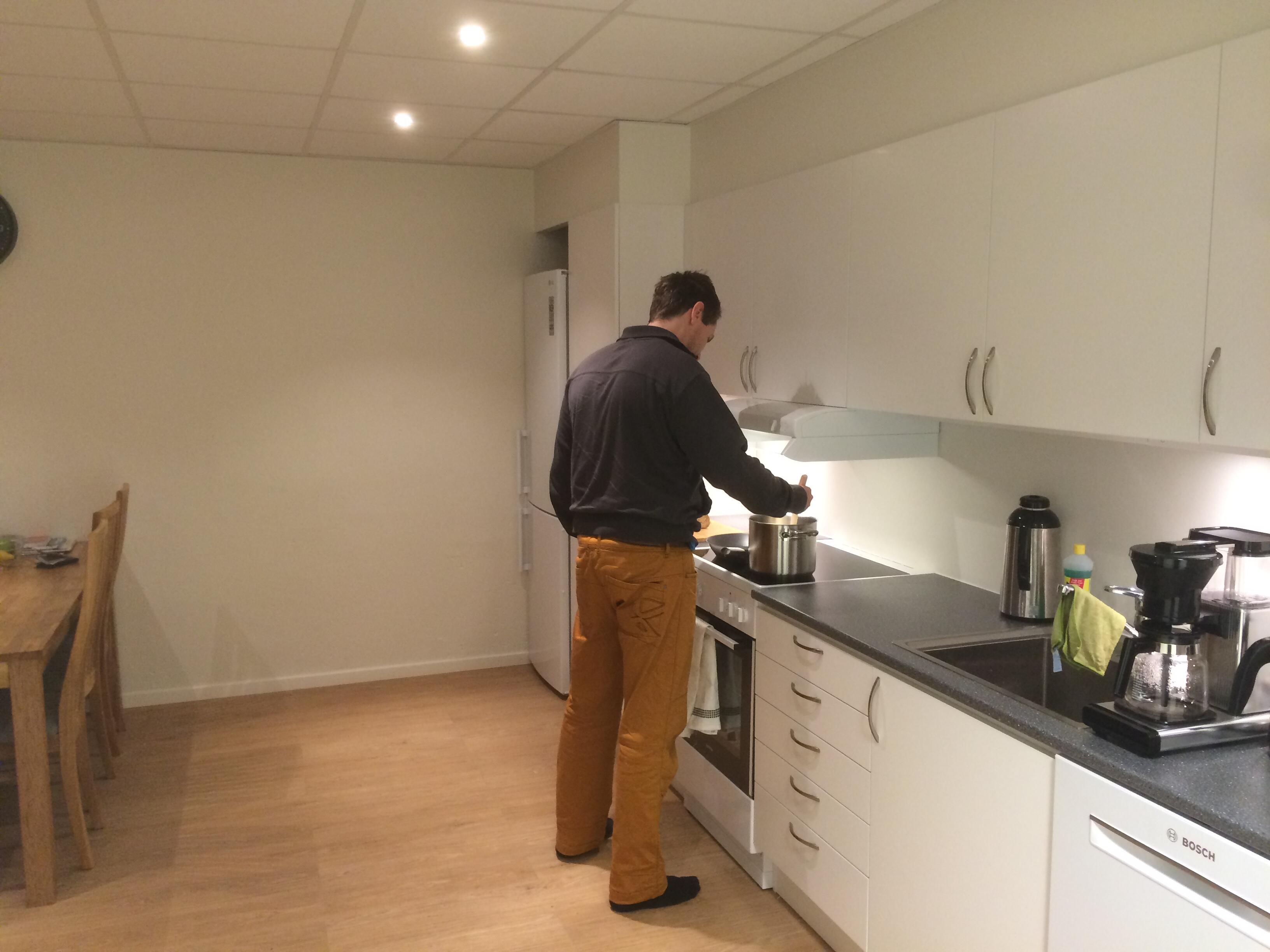 Mann lager mat på kjøkkenet