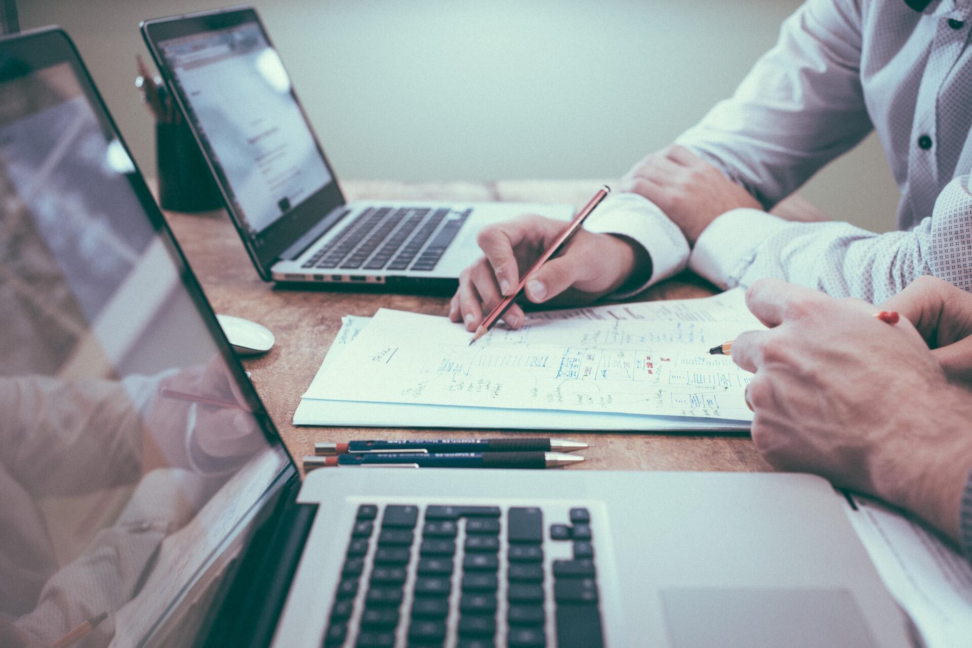 Illustrasjonsfoto av skjortekledde menn som jobber på mac-er.