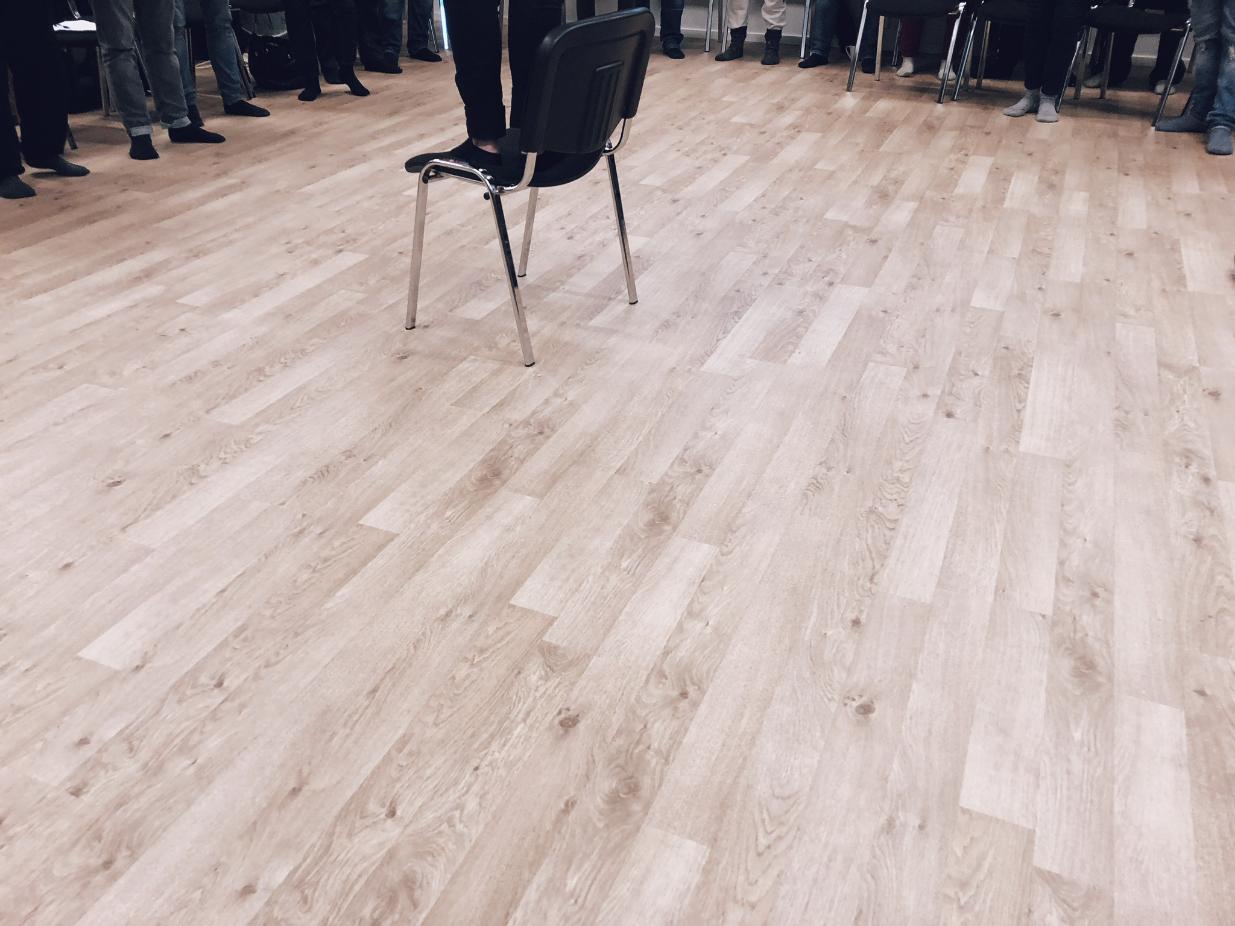 Mann som står på stol i sokkelesten. Mange andre i sokkelesten står rundt. Ingen ansikter sees.