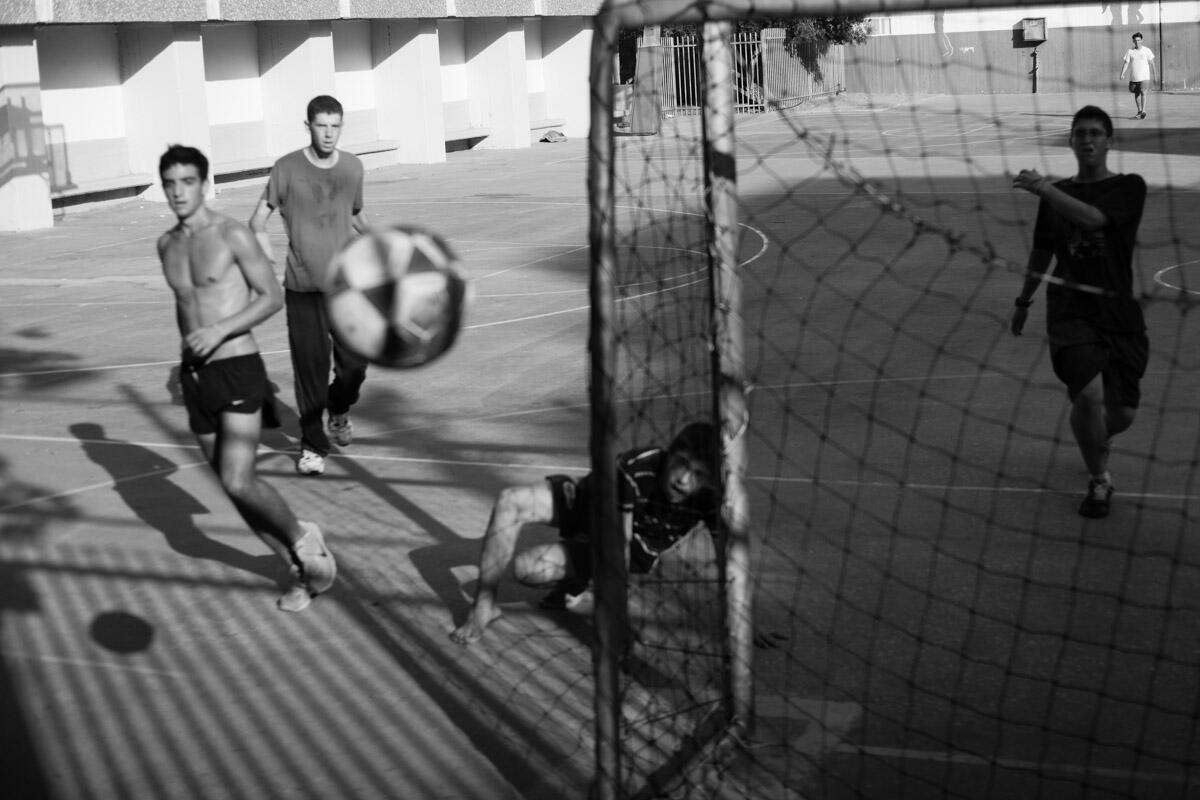 Illustrasjonsbilde i svart-hvitt av gutter som spiller gatefotball.
