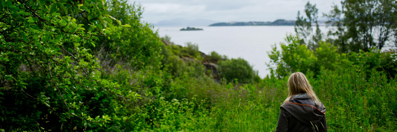 Kvinne i grønt og frodig landskap ser ut over fjorden.