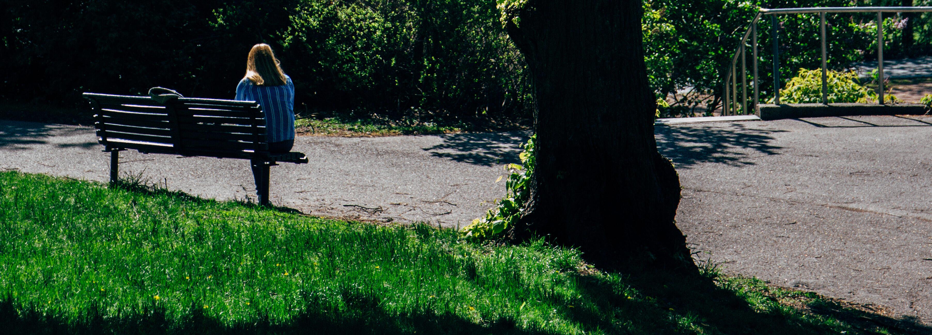 Kvinne på en benk i en park, en sommerdag.