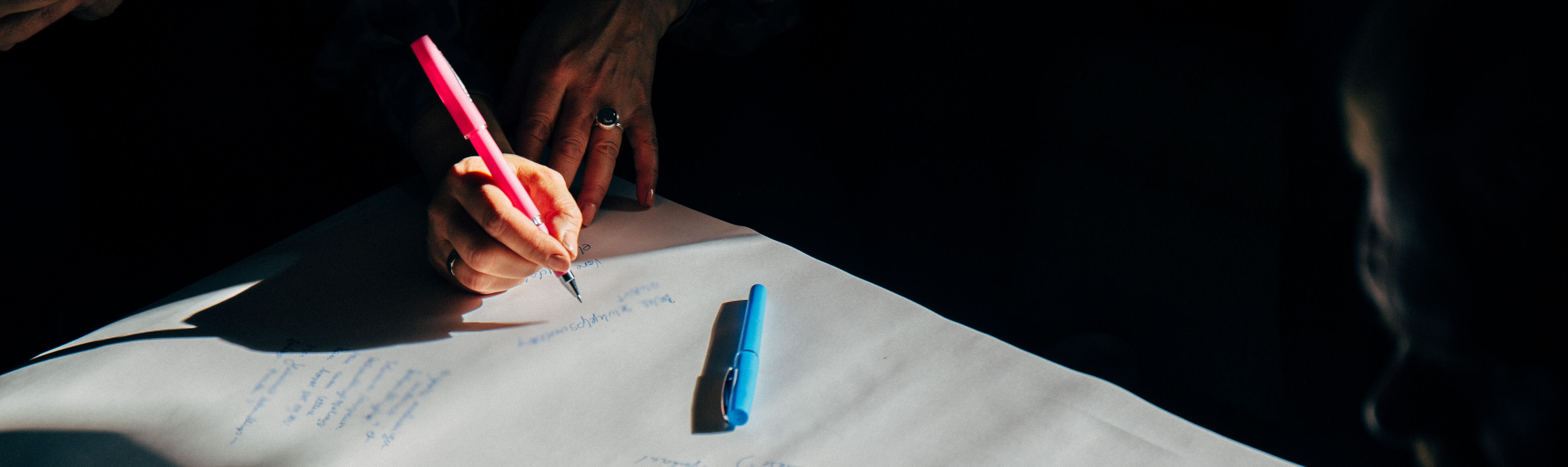 Kvinnehånd som skriver med en rosa penn.