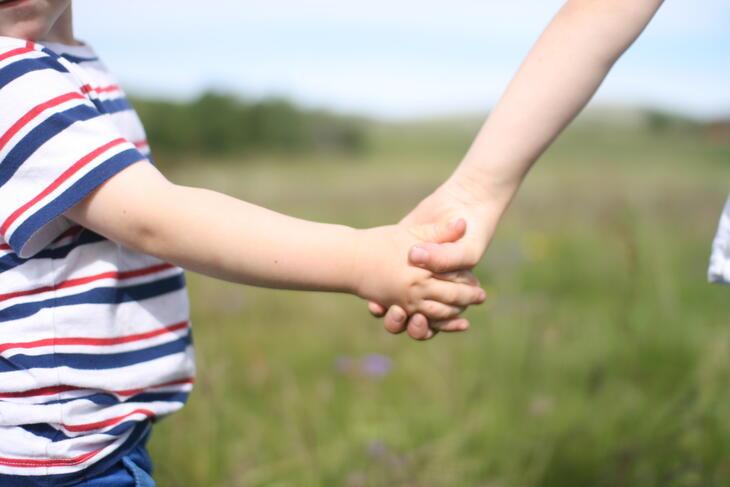 Barn og voksen som holder hender (illustrasjonsbilde)