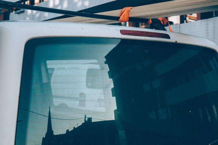 Silhuetten av et kirkespir speiler seg i bakruta på en bil med byggematerialer på taket.