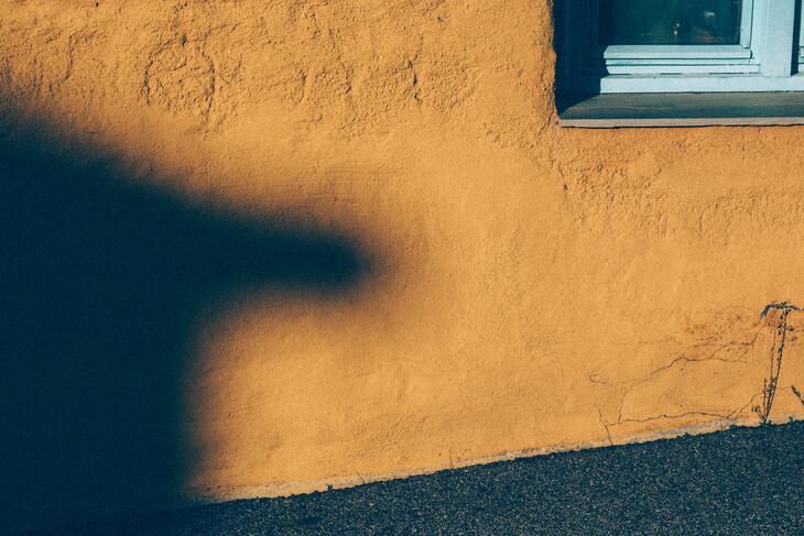 Gul vegg med skygge av takmøne.