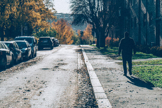 En mann går nedover en gate med trær i høstfarger.