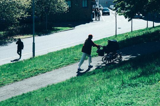 En mann triller en barnevogn på en sommerdag. En annen mann passerer.